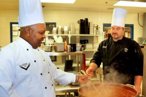 George Fortuchang (left), a resident of Christian City Skilled Nursing & Rehabilitation Center, realizes his dream to serve as a chef once again. Matt Iffland, Executive Chef of The Studio Café operated by Hanna Brothers, located at the Pinewood Atlanta Studios Production Centre, assists George in preparing the Wednesday buffet meal.