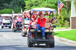 PHOTO (by Larry Regier): Active senior resident, Jan Gwaltney, waves to her neighbors as the Independence Day golf cart parade passes through one of the patio home communities at Christian City.